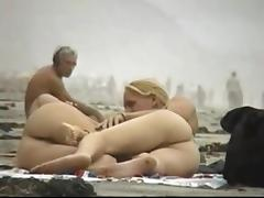 Couple play on the nude beach