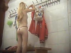 Slender blonde is taking off her dress