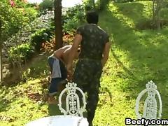 A guy in military uniform fucks a civilian guy in a park